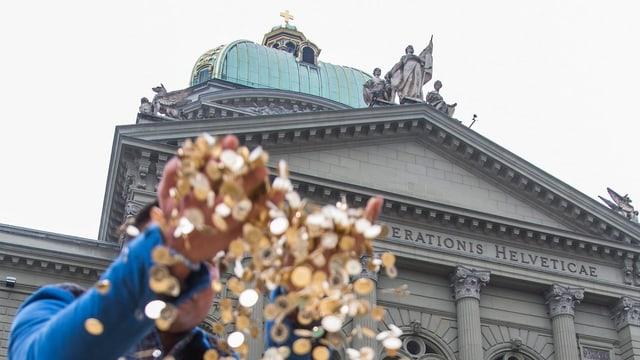 Jemand wirft zwei Hände voller 5-Rappen-Münzen vor dem Bundeshaus in die Luft.