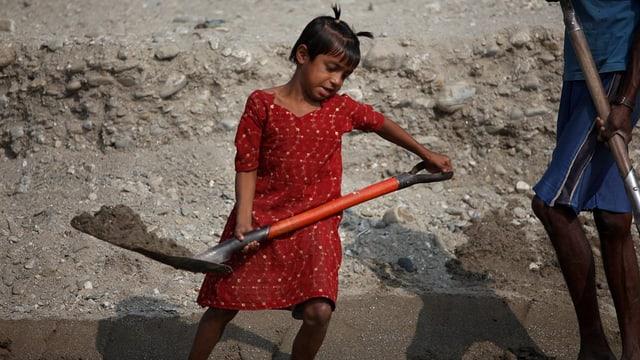 Ein indisches Mädchen schaufelt Erde.
