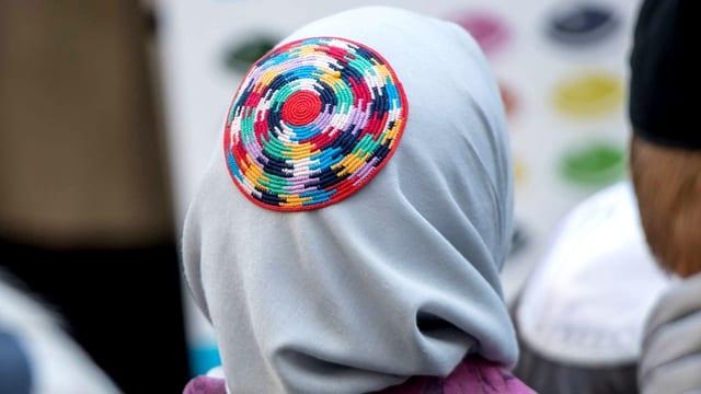 Eine Frau trägt eine Kippa über dem Kopftuch.