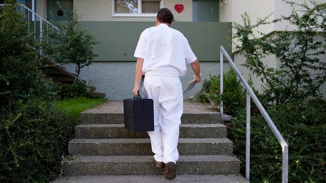 Ein Hausarzt auf Patientenbesuch schreitet eine Treppe hoch zu einer Wohung.