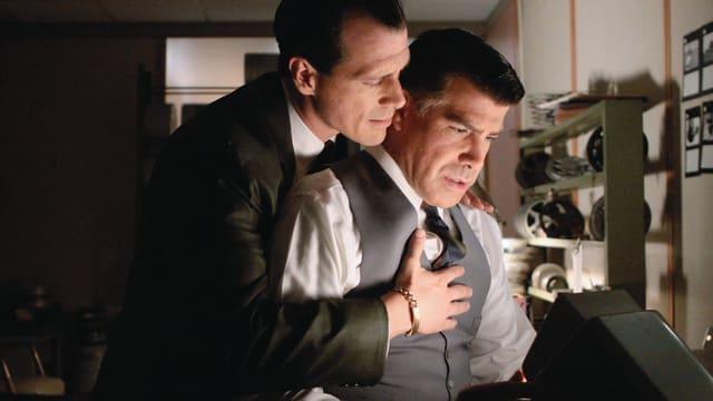 Ein Mann wird an seinem Arbeitsplatz von einem Kollegen innig umarmt.