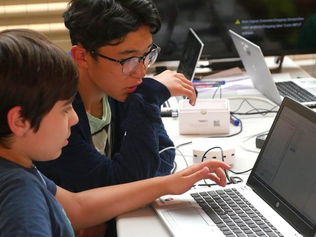Zwei Jungen schauen in einen Laptop.