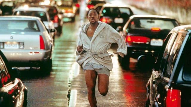 Filmszene: Will Smith rennt in Bademantel und Unterhose in der Mitte einer stark befahrenen Strasse gegen die Verkehrsrichtung.