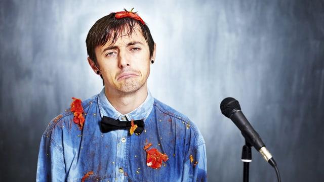 Ein Mann hinter einem Mikrophon, sein Hemd ist übersät mit Tomatenflecken.