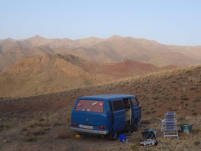 Das Bild zeigt einen blauen VW-Bus inmitten einer Wüstenregion.