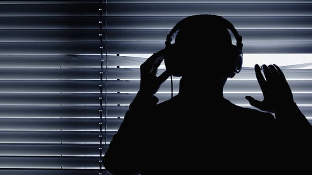 Symbolbild: Eine Person schaut durch die Lamellen einer Store nach draussen, sie hat einen Kopfhörer auf, fotografiert im Gegenlicht.