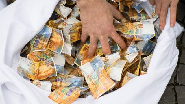 Symbolbild: Hand in einem Sack mit 10-Franken-Noten.
