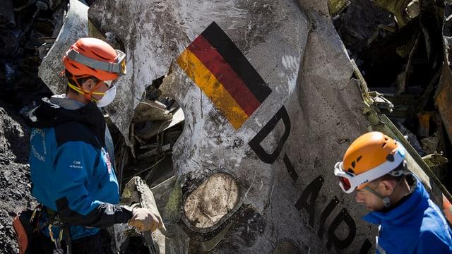 Zwei Männer und ein Trümmerteil der abgestürzten Germanwings-Maschine.
