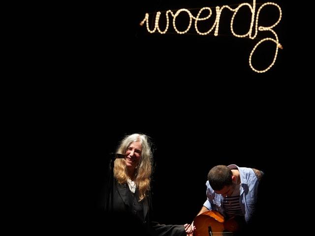 Eine Frau mit langen hellen Haaren steht auf einer dunklen Bühne, neben ihr spielt ein Mann Gitarre.