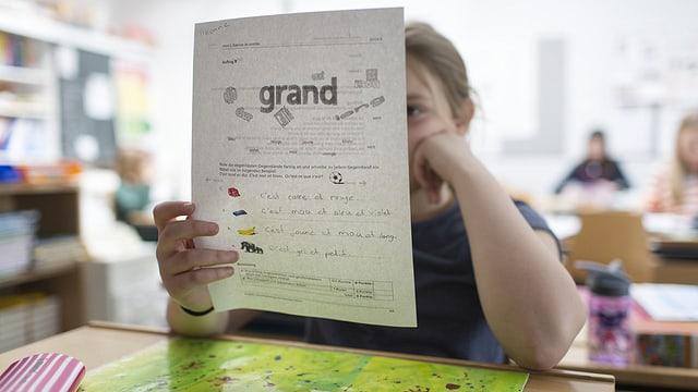 Ein Mädchen hält ein Lernblatt mit französischen Wörtern in der Hand.
