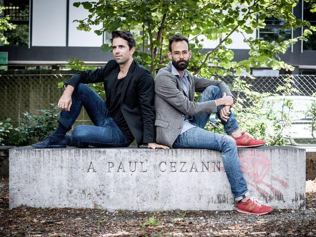 Zwei Männer sitzen Rücken an Rücken auf einer Steinbank.