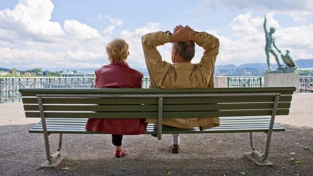 Ein älteres Ehepaar sitzt auf einer Bank und geniesst den Blick auf den Zürichsee.