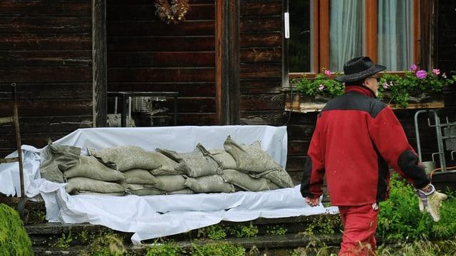 Sandsäcke vor einem Holzhaus.