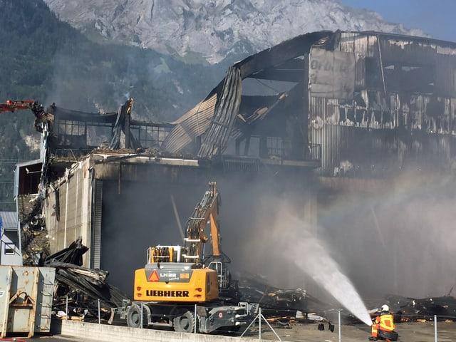 Eine zerstörte Industriehalle nach einem Grossbrand. Die Feuerwehr muss noch einzelne Glutnester bekämpfen.