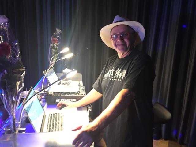 Mann mit Hut am DJ-Pult