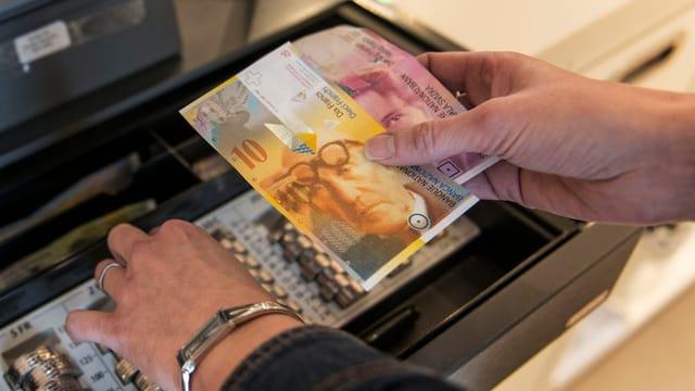 Eine Frau steht an der Kasse und hantiert mit Geld.