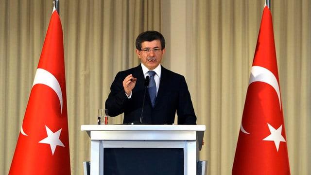 Mann steht an Rednerpult, links und rechts davon eine Türkei-Flagge