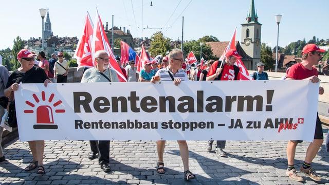 Demonstrantas e demonstrants cun in placat «Rentenalarm» a Berna.