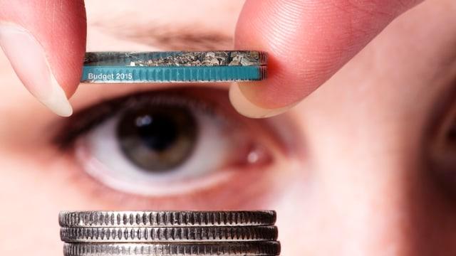 Eine Frau hält eine Münze vors Auge.