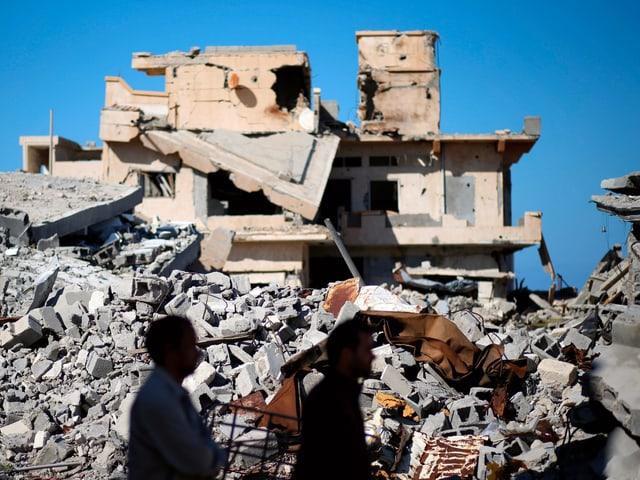 Männer vor einem Trümmerberg