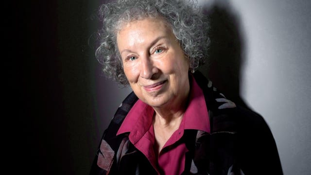 Porträt einer Frau mit purpurfarbener Bluse und grauem Haar.