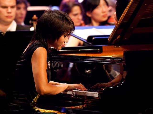 Die chinesische Pianistin Yuja Wang spielt auf einem Steinway, hinter ihr Musiker des Orchesters.