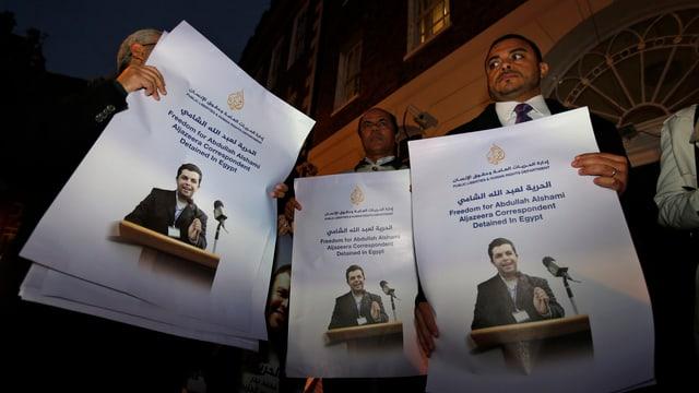 Drei Plakate mit einem ägyptischen Mitarbeiter des TV-Senders Al Dschasira