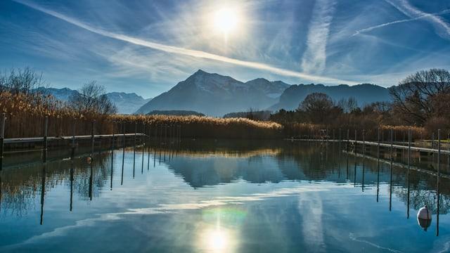 Sonne umgeben von Schleierwolken. In der unteren Bildhälfte spiegelt sich das Ganze im Thunersee.