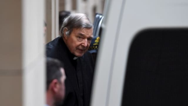 George Pell che entra en in bus da polizia.