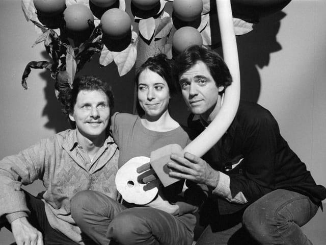S/W-Bild: Zwei Männer und eine Frau sitzen vor einer Art gebasteltem Baum. Es sind die drei Mitglieder des Trios Mummenschanz mit einem selbstgebastelten Requisit.