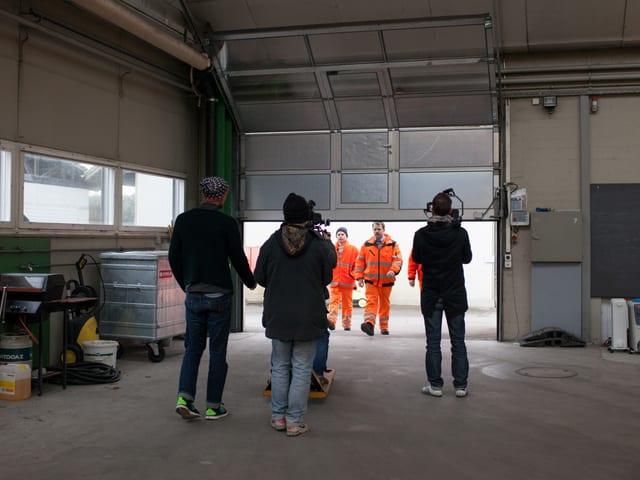 Im Vordergrund stehen mit dem Rücken zum Betrachter Kamera- und Tonmänner, daher laufen die drei Abfalldetektive ins Bild.