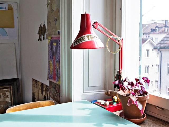 Tisch und rote Tischlampe, die auf dem Fenstersims einer Altbauwohnung steht.