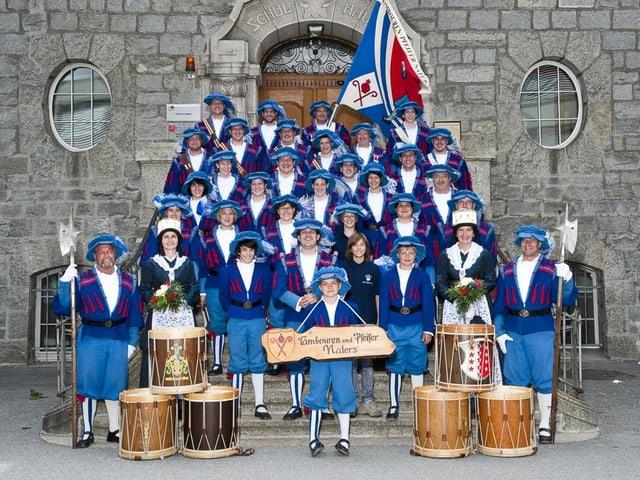 Die Pfeifer und Trommler in blauen Uniformen haben sich auf eine Treppe fürs Foto gruppiert.