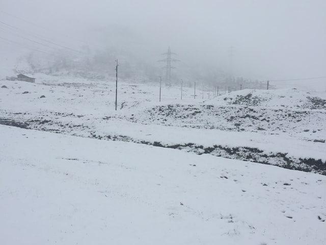 Dunkle Wolken dominieren das Bild. Eine Schneeschicht überzieht die Wiesen und Steine.