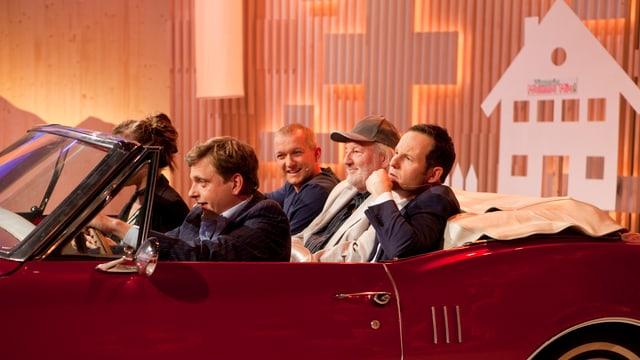 Simon Enzler, Peach Weber und Claudio Zuccolini sitzen im Auto, vorne sitzen zwei Schauspieler.
