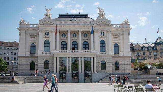 Das Zürcher Opernhaus von aussen aufgenommen bei Sonnenschein. Passanten laufen vor dem Gebäude durch.