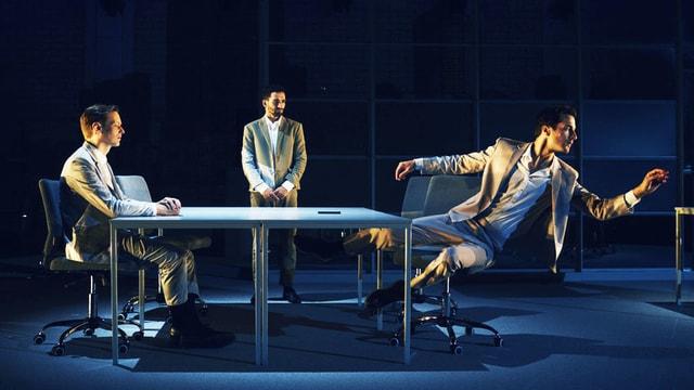 Zwei Männer in Anzügen sitzen an einem Tisch. Dahinter steht ein Dritter, ebenfalls im Anzug.