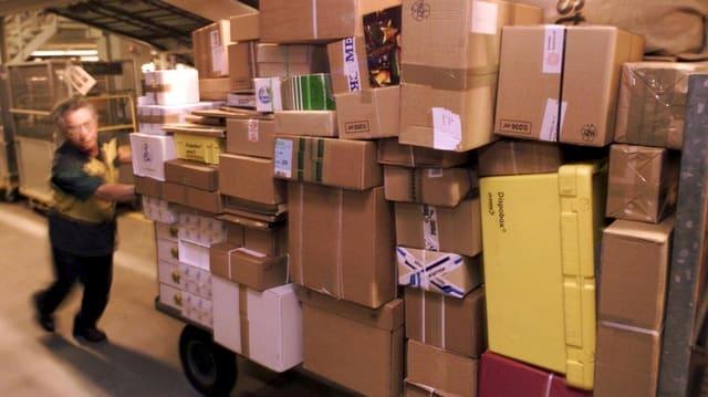 Ein Mitarbeiter der Post schiebt einen Wagen mit vielen Paketen.