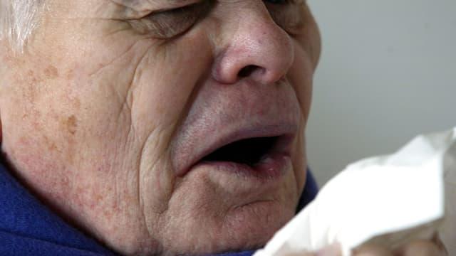 Ein Mann niest in ein Taschentuch.