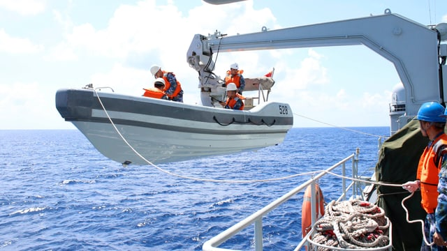 Ein Beiboot wird mit einem Kran vom Mutterschiff ins Wasser gelassen.