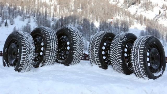 Sechs Winterreifen in einer Schneelandschaft.