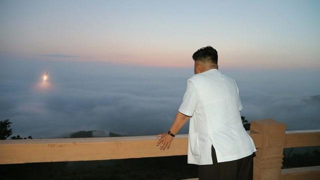 Kim in weissem Hemd, durch die Wolken bricht eine startende Rakete.
