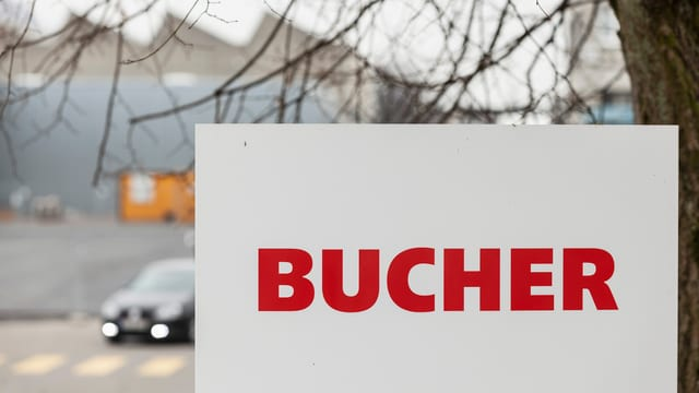 Ein Schild der Firma Bucher steht vor einer Strasse, auf der ein Auto durchfährt.