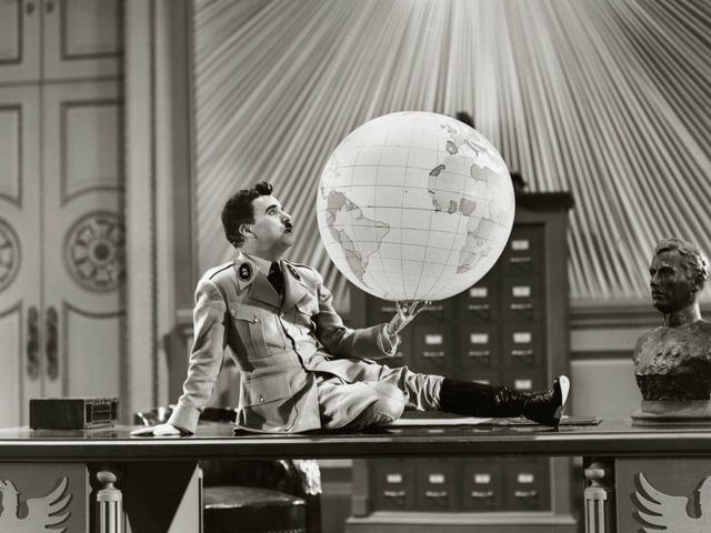 Mann mit Uniform sitzt auf einem Schreibtisch und hält eine Weltkugel in der Hand.