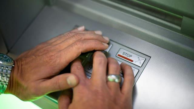Hände auf der Tastatur eines Bankomats