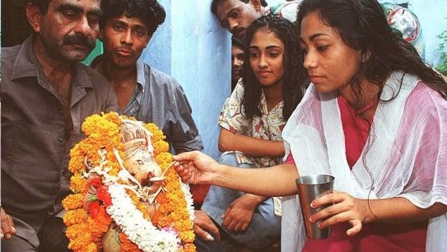 Eine Frau füttert eine Ganesh-Statue mit Milch.