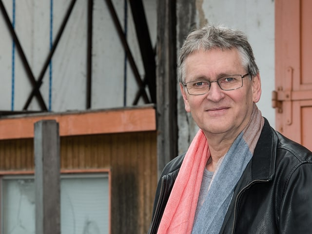 Ein Mann mit farbigem Schal und schwarzer Lederjacke