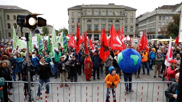 Demonstranten mit Fahnen stehen auf dem Bundesplatz