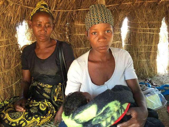 Zwei Frauen sitzen in einer Hütte