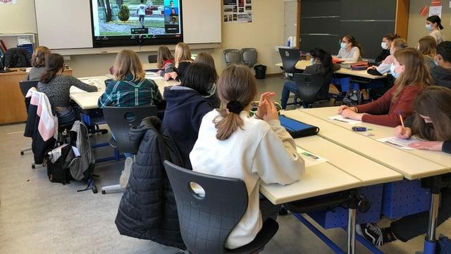 Schülerinnen und Schüler blicken in einem Klassenzimmer auf eine Leinwand